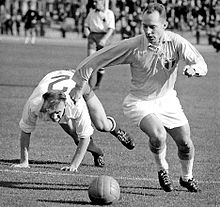 "A black-and-white action shot taken in the midst of an association football match. To the viewer's right a player in light shirt, white shorts and white socks turns to his right, his eyes pointed down towards the ball. A shield bearing the letters ""MFF"" is prominently displayed on his shirt. Behind him, an opposing player in a white shirt can be seen stumbling mid-chase, throwing his arms forward to break his fall."