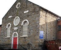 Symmetric stone-faced front of a small chapel with a round window above a red door and two windows to either side