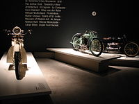 "Three pristine 1920s - 1930s motorcycles on pedestals in front of text printed on the wall with words relevant to the period, such as ""Prohibition"" and ""Al Jolson""."