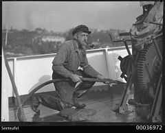 Boatswain Karl Muller smoking a pipe and hosing the deck of SEETEUFEL (9611943840).jpg