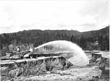 Photo of miners spraying water into a placer