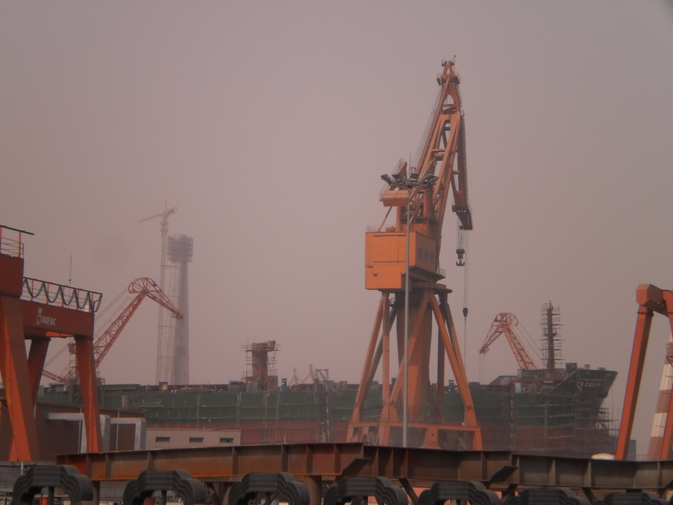 An unfinished ship and an orange crane at the center of an industrial setting