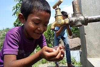 Human right to water and sanitation - Image: Boy drinks from a tap at a NEWAH WASH water project in Puware Shikhar, Udayapur District, Nepal. (10677936093)