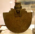 Bronze Aegis of Isis. She wears a tripartite wig with 12 uraeus serpents. From Saqqara, H5-228, Egypt. Ptolemaic period, 30th Dynasty. The Petrie Museum of Egyptian Archaeology, London.jpg
