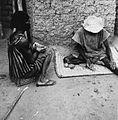 COLLECTIE TROPENMUSEUM Een ritueel specialist 'leest' de kaurischelpen voor een vrouw tijdens een consult TMnr 20010336.jpg