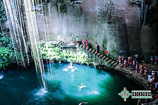 cenote with blue water and tourists jumping from a platform