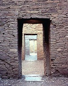 A rectangular entrance through a thick wall dressed with sandstone blocks in the foreground. The entrance reveals a view of another similar wall, itself bearing a doorway showing yet another wall with another door. Four such nested sets of doorways are seen, with a fifth wall visible through the final fourth doorway.