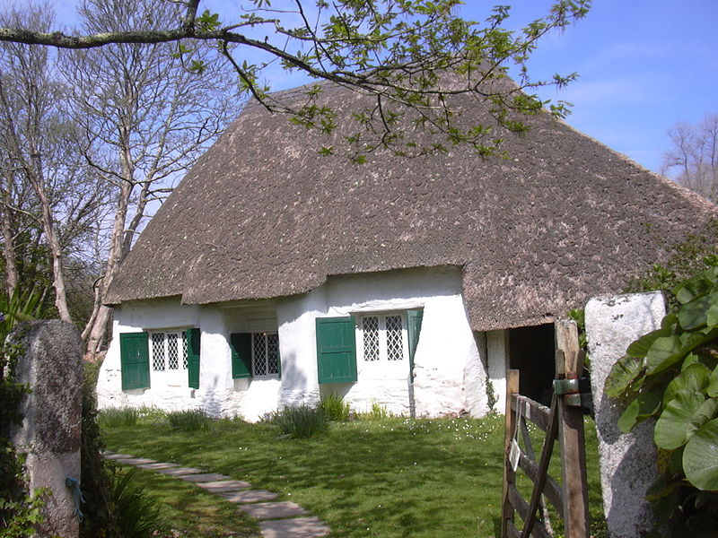 a thatched building, with white walls and green shutters on the windows, sits in the sunshine