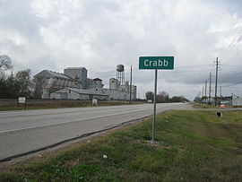 Crabb road sign on FM 762 looking west with disused grain elevator on left and businesses on the right