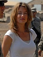A woman with brunette hair, wearing a white t-shirt.