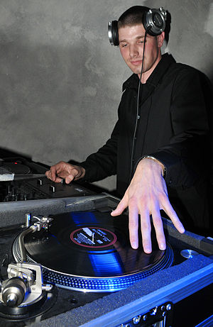 DJ mixer -  A disc jockey performing at the 2009 Air Force Ball. With one hand he is manipulating a vinyl record on a turnable; the other hand is controlling the mix with a DJ mixer.