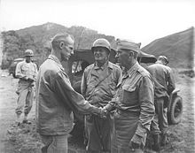Two men in uniform shake hands. One is bear headed; Krueger wears his garrison cap. With them is a man wearing a steel helmet. A jeep is parked behind them.