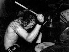 Bubeník Dave Grohl hraje na bicí soupravu.  Nemá na sobě košili a dlouhé vlasy mokré.