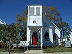 Small white clapboard church. The entrance is on the left, under another story just above the entrance, which gives the church a lopsided appearance.