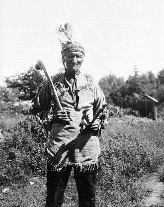 Wasauksing First Nation - Dick King, Potawatomi, photographed in 1928 on Parry Island. King is  holding a war club  and dance rattles, both now in the NMAI Collection.