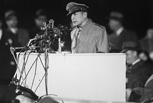 MacArthur at a podium with a gaggle of microphones in front of him. Men in suits and hats sit behind him.