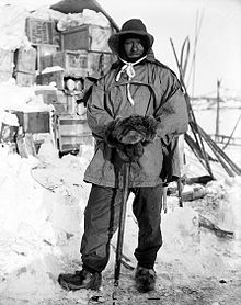 Full length picture of a man wearing heavy, Arctic clothing. He is standing outside in front of a snow-covered stack of wooden crates