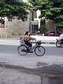 Elementary school student riding bike in downtown Yogyakarta during the 2010 Merapi Eruptions.jpg