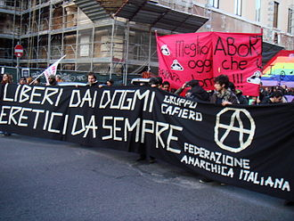 "Contemporary anarchism - Contemporary members of the Italian Anarchist Federation marching in Rome in 2008 in an anti-catholic church manifestation. The text translates as ""free from dogmas, always heretics"""