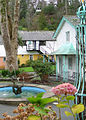 Flowers, pastel houses, courtyard with spouting fountain (Portmeirion, December 2004).jpg