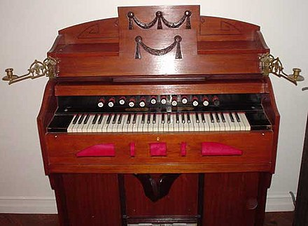 A harmonium. Operation of the two large pedals at the bottom of the case supplies wind to the reeds. Footpropelled organ.jpg