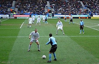 Association football positions - A defender (in the foreground, wearing a white shirt) challenging for possession
