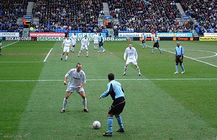A defender (in the foreground, wearing a white shirt) challenging for possession Fulham on the attack.jpg