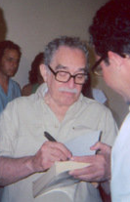 Grey haired man with a moustache and glasses stands while autographing books.
