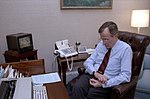 George H. W. Bush watches television as he checks his watch.jpg