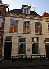 foto van Huis met gepleisterde lijstgevel met in de verdieping schuiframen en dakvenster met balustrade