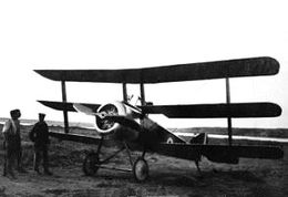 Front three-quarter view of military triplane on landing ground, with two men standing beside it