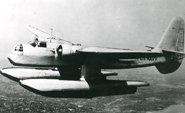 A twin-engined, monoplane aircraft, fitted with two large floats and with a large tail fin, flies over a city.