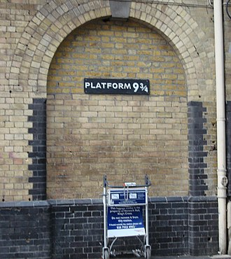Harry Potter and the Philosopher's Stone - Imitation of the fictional Platform 9¾ at the real King's Cross railway station, with a luggage trolley apparently halfway through the magical wall