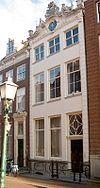 foto van Zandstenen gevel opgericht voor ouder pand; geblokte hoeklisenen en rijk geornamenteerde kroonlijst met opzetstukken en hoekvazen. Stoep met stoephek. Inwendig stucwerk in gang en vestibule, voorkamer met gesneden deur en stucplafond in Lodewijk XIV-vormen