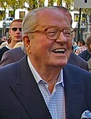 An elderly white man with receding white hair is wearing glasses. He is outdoors with various people in the background, suggesting a crowd. He is smiling, his mouth open. He is wearing a shirt with a blue jacket.