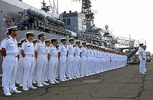 Japanese sailors lined up on a quay in front of a warship