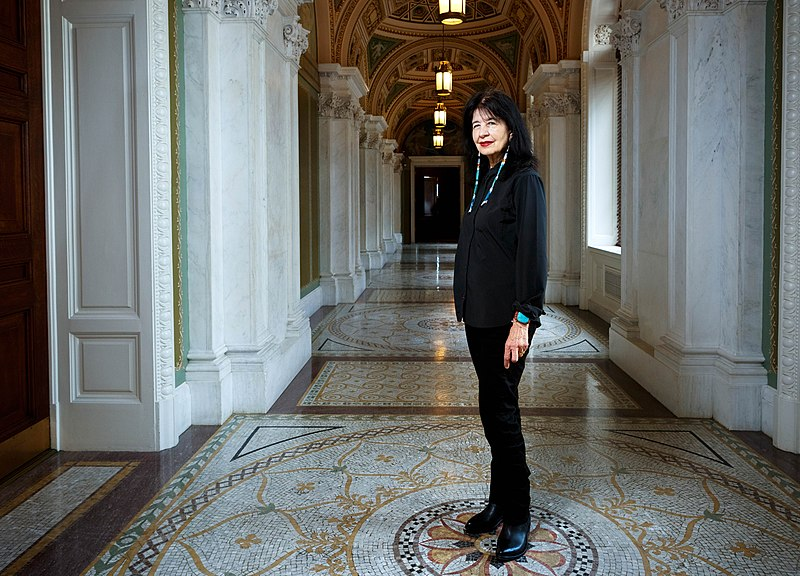 Joy Harjo stands in the middle of a marble hall, with a large turquoise bracelet and red lipstick, smiling at the camera.