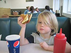 Child eating a veggie burger at a fast food re...