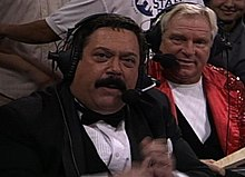 Two men wearing headsets to commentate a professional wrestling event