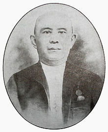 A black and white photograph of a bald Chinese man looking forward