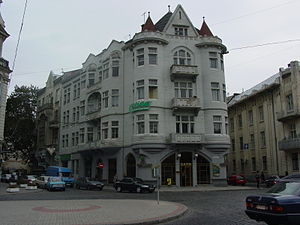 A streetscape, with a neo-gothic greyish-white building with turrets and balconies.