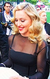 Madonna in a black dress, smiling and looking down