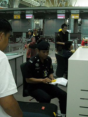 Auxiliary police - A Malaysia Airport auxiliary police officer examining a list of luggage being scanned at Kota Kinabalu International Airport.