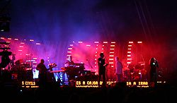 Seven musicians on a brightly lit stage sing into microphones and perform various musical instruments. They play against a multi-color background with scrolling text by their feet.