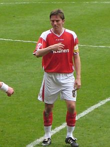 A brown-haired footballer in a red-and-white shirt, shorts and socks with his right arm across his chest, standing on a football pitch