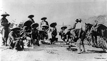 A group of 14 armed men, eight of them crouching down, in sombreros and holding rifles