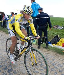 A cyclist wearing a yellow and gray cycling jersey, riding over cobblestones. Spectators on the roadside are looking behind him, out of the frame.