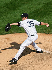 A man standing on a pitcher's mound stretches to throw a baseball from his right hand