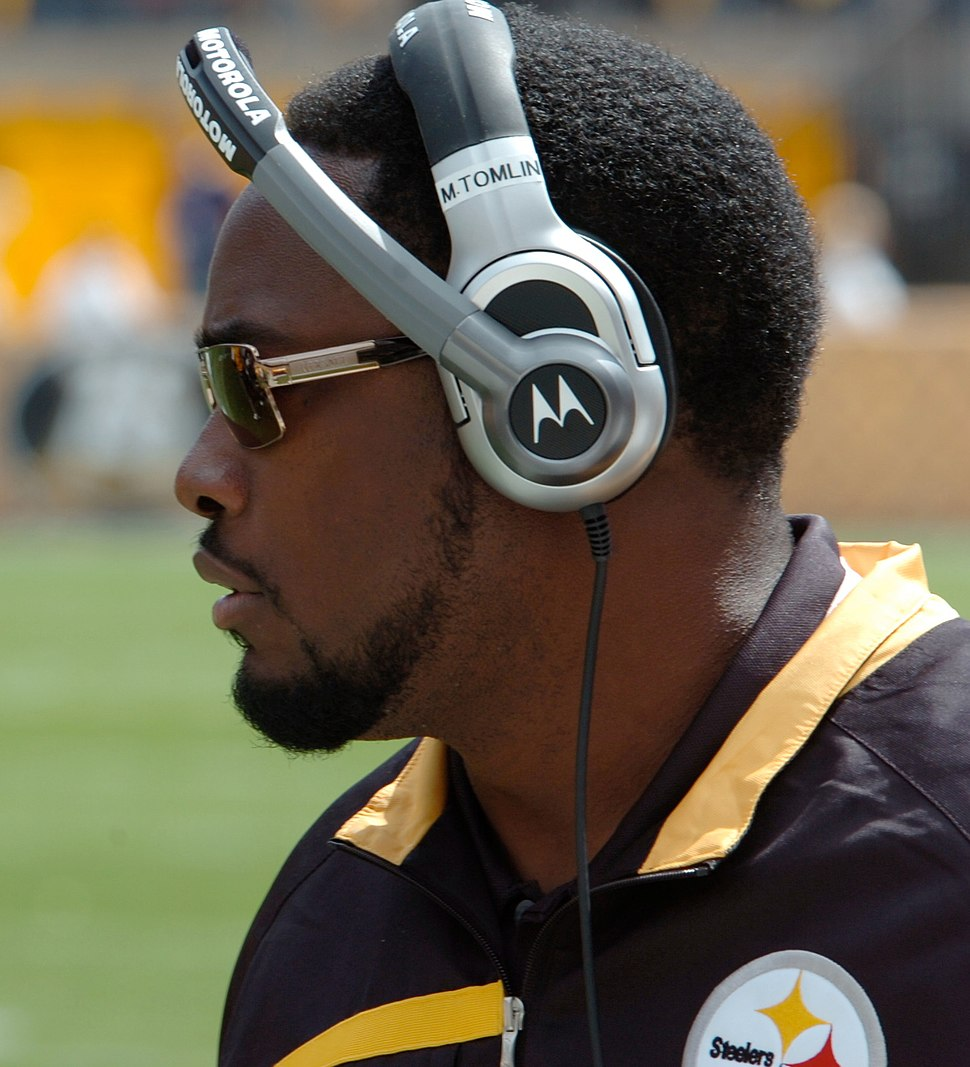Color head shot of African-American man (Mike Tomlin) in profile on a football sideline wearing a black and gold Pittsburgh Steelers jacket, Motorola headset and sunglasses.