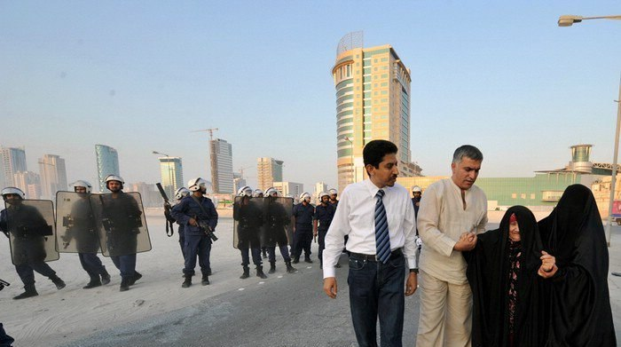 Nabeel Rajab and Abdulhadi Alkhawaja helping an old woman after police attacked a peaceful protest in August 2010